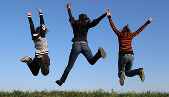 Three young people jump in the air